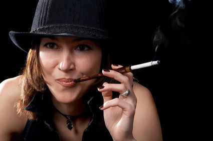 Woman in hat with cigarette holder isolated on the black background