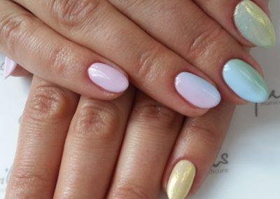 Manicure hybrydowy w pudrowym kolorach zaakcentowany mieniącym się pyłkiem
