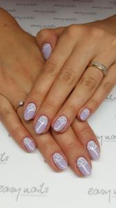 Delikatny beżowy manicure hybrydowy z białymi ornamentami